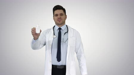 fidedigno : Doctor presenting nasal spray or some other medicine on gradient background. Stock Footage