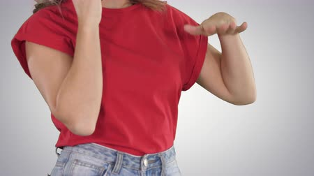 hívó : Woman in red t-shirt making gestures while talking on the phone on gradient background.