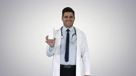 recipient : Confident Doctor Smiling and Presenting in Hand New Treatment on gradient background. Stock Footage
