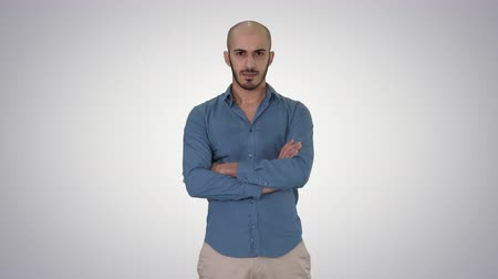 hajtogatott : Serious confident arabian man in casual folds hands looking into camera on gradient background.