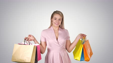 pitka : Shopping woman happy smiling holding shopping bags iwhile walking on gradient background.