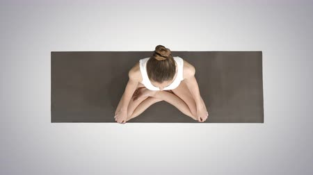 restorative : Young sporty woman practicing yoga sitting in lotus pose and breathing deeply on gradient background. Stock Footage