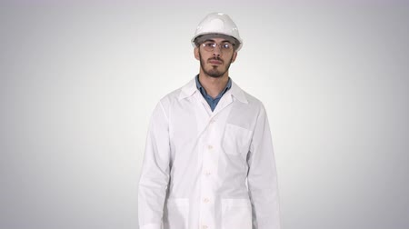 manipulacja : Young engineer in robe and helmet putting glasses on while walking on gradient background. Wideo