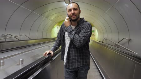 гласность : Handsome caucasian man making a call on escalator. Стоковые видеозаписи