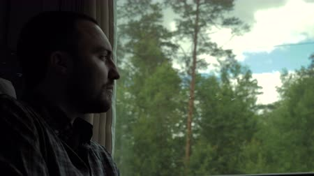 cansado : Caucasian man in a train in daytime, looking out window.