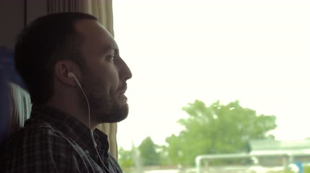 stair : A Man listening to the music with earbuds from a smart phone in a train. Stock Footage