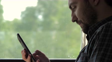 Handsome man surfing in web with his smartphone in a train.