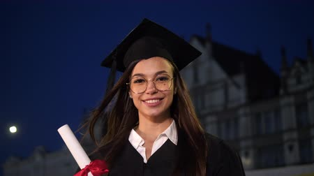 master's degree : Happy beautiful young female graduate smiling to camera. Stock Footage
