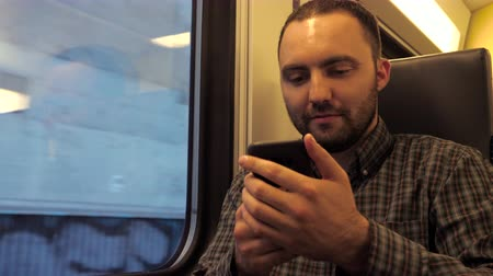close cropped : Handsome man sitting in a subway train and surfing in web with his smartphone.