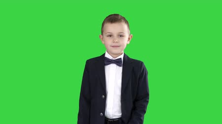 школьник : Boy in formal costume walking with a hand in pocket on a Green Screen, Chroma Key. Стоковые видеозаписи