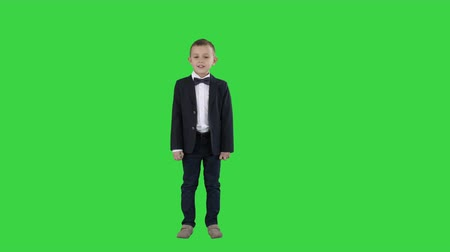smokin : Boy in a suit walks in a frame and starts talking on a Green Screen, Chroma Key.