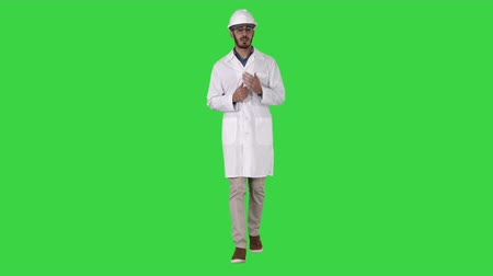 здесь : Scientist in white robe and helmet presenting pointing to side with hand and explaining to camera on a Green Screen, Chroma Key.