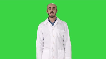 クリップボード : Friendly male doctor walking and talking looking in camera on a Green Screen, Chroma Key. 動画素材
