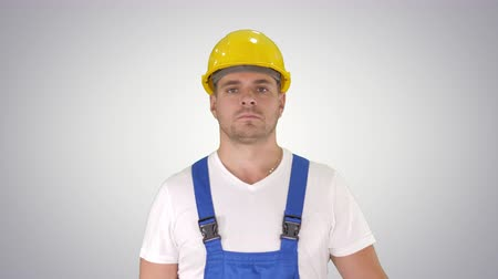 строгий : Builder walking and looking to camera on gradient background.