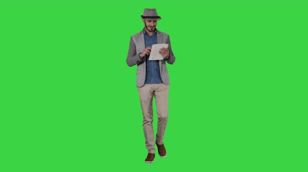 Handsome smiling arab man in a hat walking and using tablet on a Green Screen, Chroma Key.
