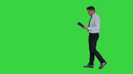 путаница : Young confused man trying to read smart book misunderstanding content while walking on a Green Screen, Chroma Key.