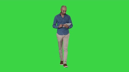 Arabian man walking and using tablet surfing internet on a Green Screen, Chroma Key. Stockvideo