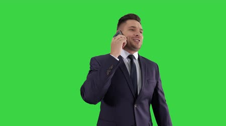 Businessman talking on mobile phone happily on a Green Screen, Chroma Key.