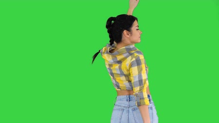 Happy woman in jeans shorts dancing on a Green Screen, Chroma Key. 影像素材