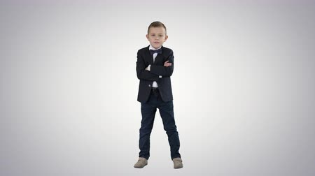hajtogatott : Little boy kid crossing hands in a formal costume on gradient background. Stock mozgókép
