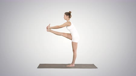 Beautiful young fit woman in sportswear doing sport exercise, bending in variation of Utthita Hasta Padangusthasana, Dandayamana-Janushirasana, Standing Head to Knee Bikram posture on gradient background.