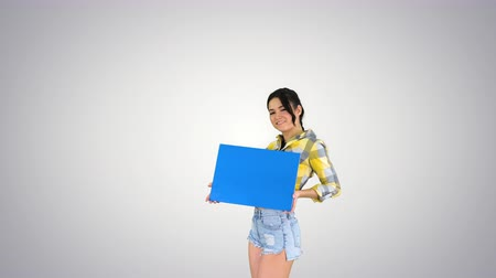 здесь : Young charming brunette model holding empty board on gradient background. Стоковые видеозаписи