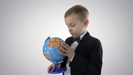 Happy schoolboy in a formal suit studying a globe on gradient background. Stockvideo