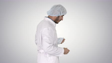 опытный : Arabic doctor walking and putting medical cap on on gradient background.
