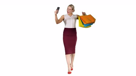 comprimento : �¡heerful woman with shopping bags taking selfie on white background. Stock Footage