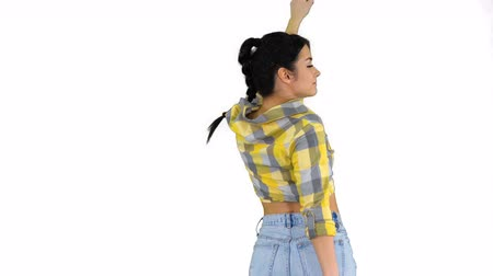 houska : Happy woman in jeans shorts dancing on white background.