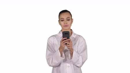 genérico : Cheerful cute young woman doctor typing text on phone while walking on white background.