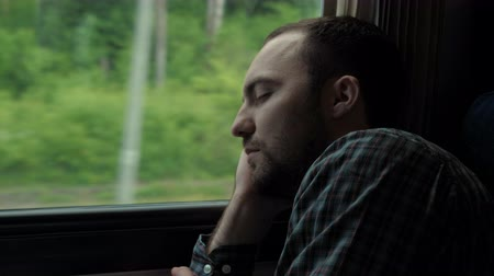 rekesz : Young man traveling on a train and sleeping dreaming.