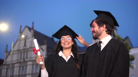 master's degree : Funny graduates in academic gowns dancing and fooling around after graduation.