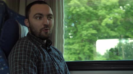 train workers : Attractive man talking to camera while riding a train. Stock Footage