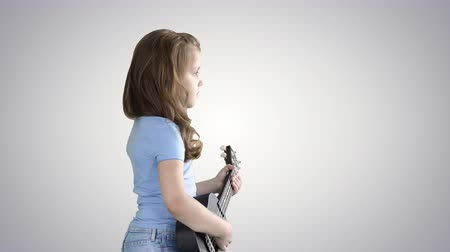 risonho : A little girl walking with ukulele in hands on gradient background.