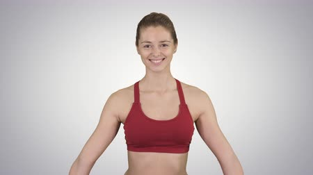 cipőfűző : Young attractive woman practicing yoga, sitting in Gomukasana exercise, Cow Face pose, while being photographed on gradient background. Stock mozgókép
