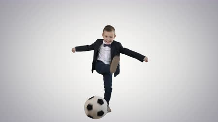 red shoes : Little Boy In Costume Shooting at Goal on gradient background.