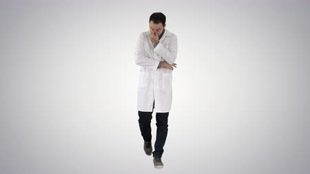 čelo : Tired doctor walking on gradient background.