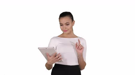 стоять : Serious attractive young woman or student reading information on a tablet computer on white background.