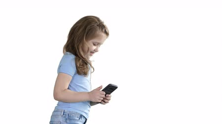 telefonda : Little girl is playing with smartphone while walking on white background.