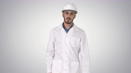 multikulturális : Arab engineer in helmet and white robe walking forward on gradient background. Stock mozgókép