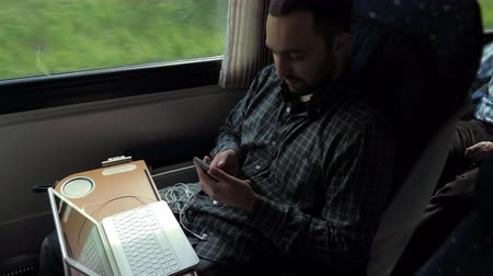 first class : Businessman Commuting To Work On Train Using Mobile Phone.