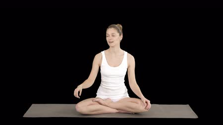directing : Young attractive woman sitting in lotus pose and pointing at something or someone while talking, Alpha Channel