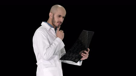 radiologia : Young male physician reading and reviewing a MRI brain scan while walking, Alpha Channel
