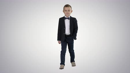 delikanlı : Boy in formal costume walking with a hand in pocket on gradient background.