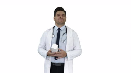 describing : Mature doctor in whitecoat describing new pills in box on white background. Stock Footage