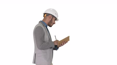 hard hat : Arabic man in casual clothes and hard hat writing down checklist on white background.