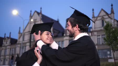 bakalář : Happy couple of graduates looking at each other.
