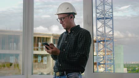 joyfulness : Constructor or engineer listening music on headphones from his phone during break.