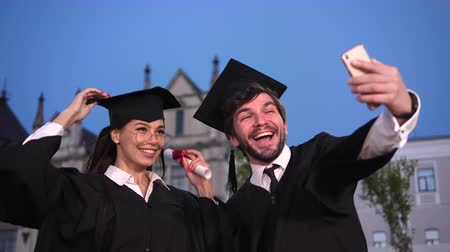 graduação : Happy male and female graduate students taking a selfie. Stock Footage